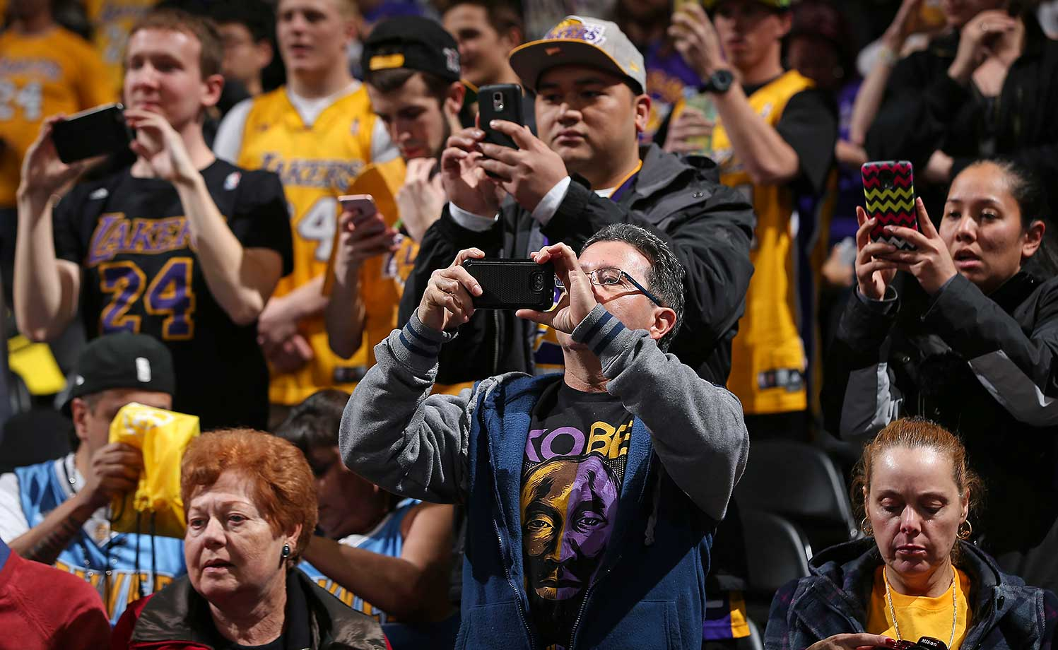 Fans try to capture a photo of Kobe Bryant as he warms up prior to facing the Denver Nuggets.