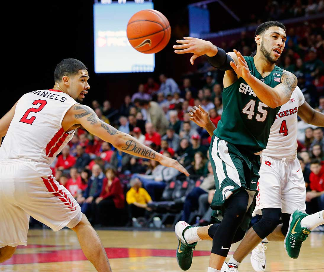 Player of the Year candidate Denzel Valentine of Michigan State passes as Bishop Daniels of Rutgers defends.