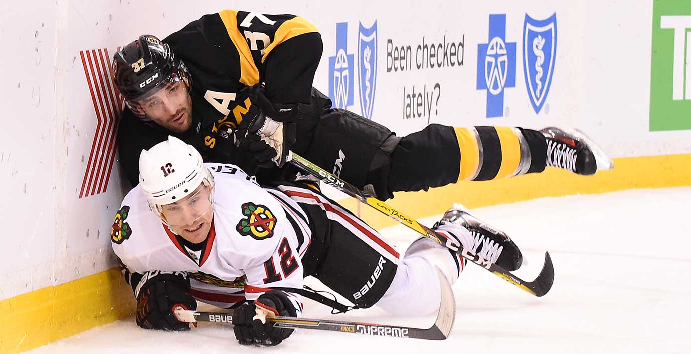 Patrice Bergeron of the Boston Bruins collides with Tomas Fleischmann of Chicago.