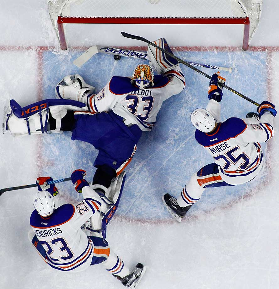 Edmonton's Cam Talbot blocks a shot by Philadelphia's Sean Couturier (not shown) as Matt Hendricks (23) and Darnell Nurse (25) also defend.
