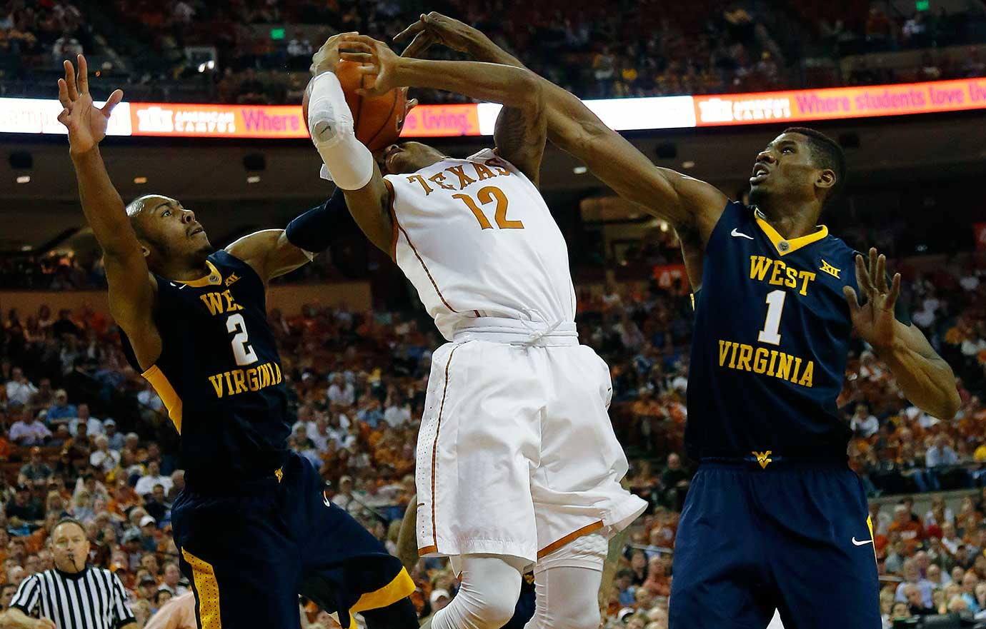 Kerwin Roach Jr. of Texas is fouled while shooting between Jevon Carter, left, and Jonathan Holton of West Virginia.