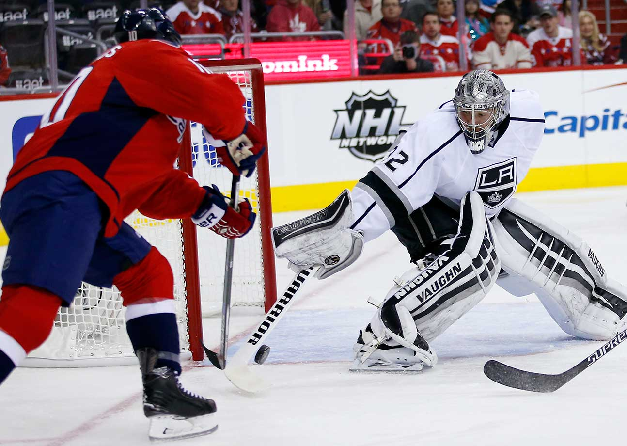 Washington Capitals center Mike Richards reaches for the puck with Los Angeles Kings goalie Jonathan Quick.