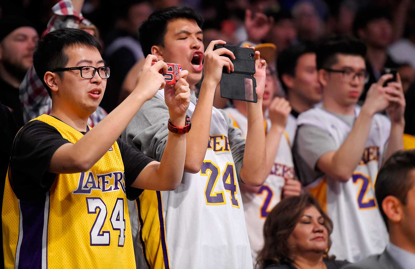 Fans wearing Kobe Bryant jerseys take photos in Los Angeles. The Lakers won 119-115.