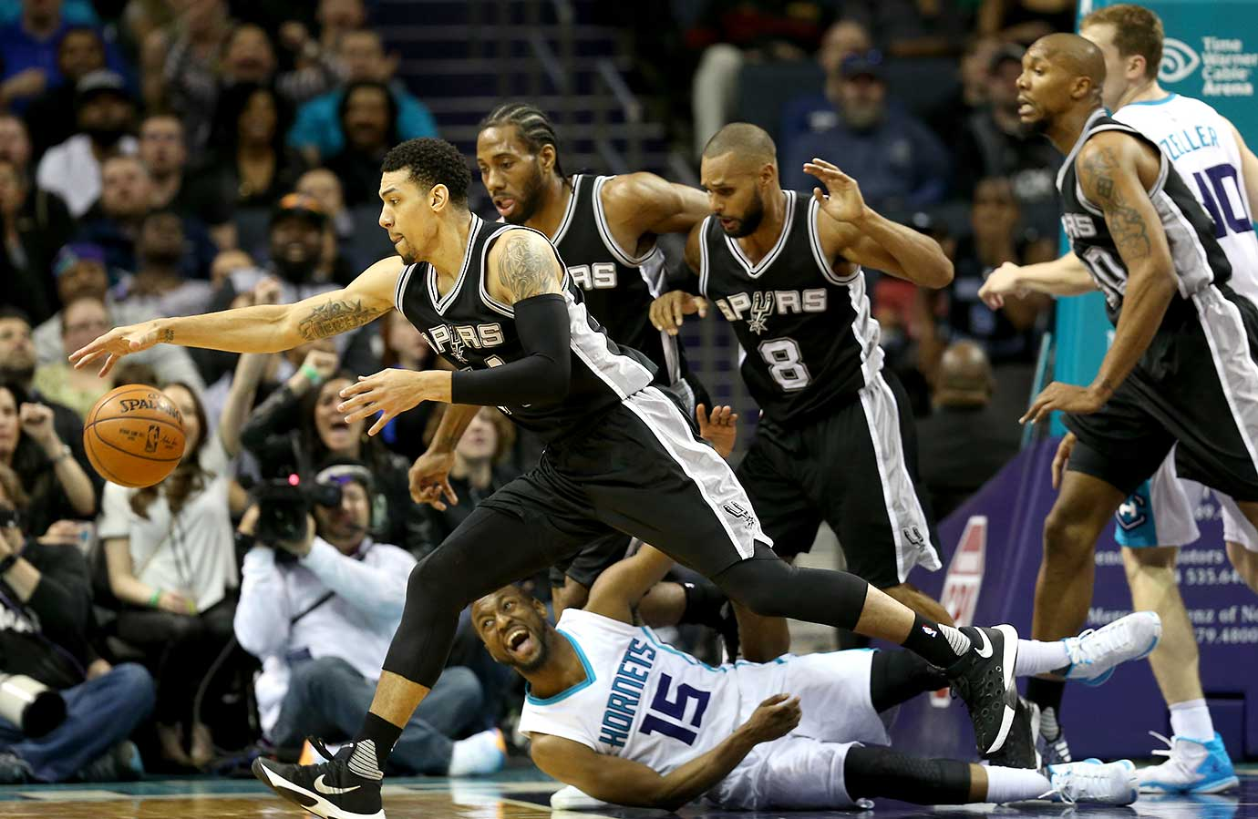 Kemba Walker of the Charlotte Hornets watches as Danny Green of the San Antonio Spurs goes after a loose ball.