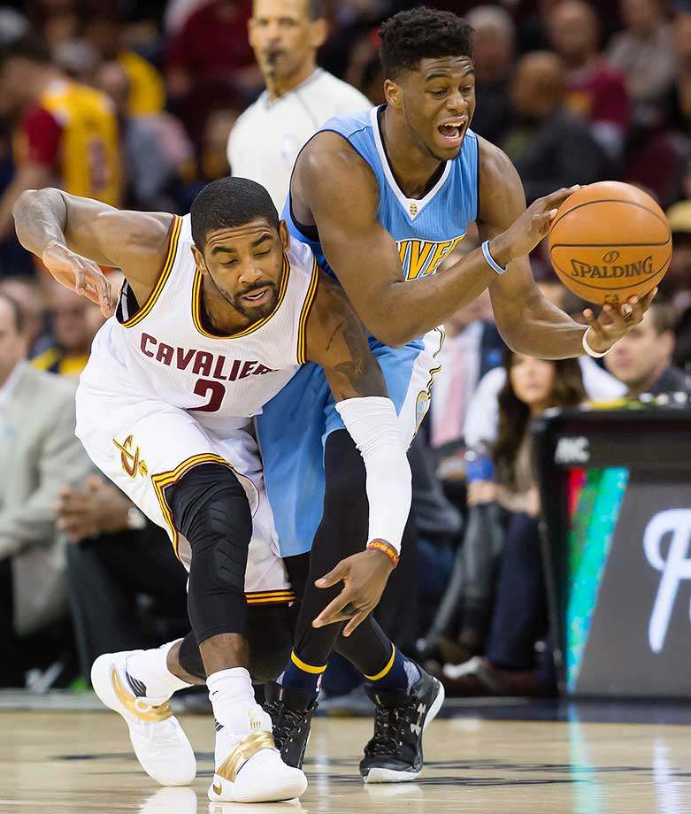 Kyrie Irving of the Cleveland Cavaliers tries to steal from Emmanuel Mudiay of the Denver Nuggets.