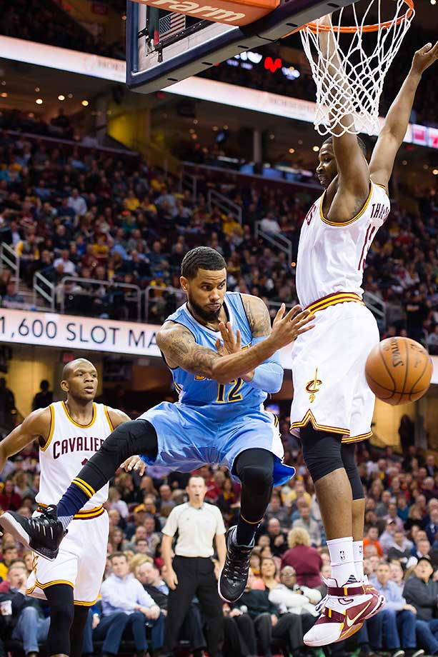 D.J. Augustin of the Denver Nuggets passes around Tristan Thompson of the Cleveland Cavaliers.