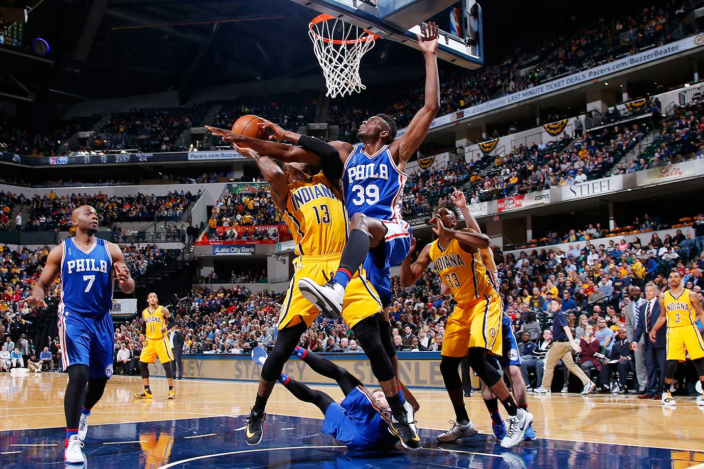 Paul George of the Indiana Pacers is fouled by Jerami Grant of the Philadelphia 76ers.