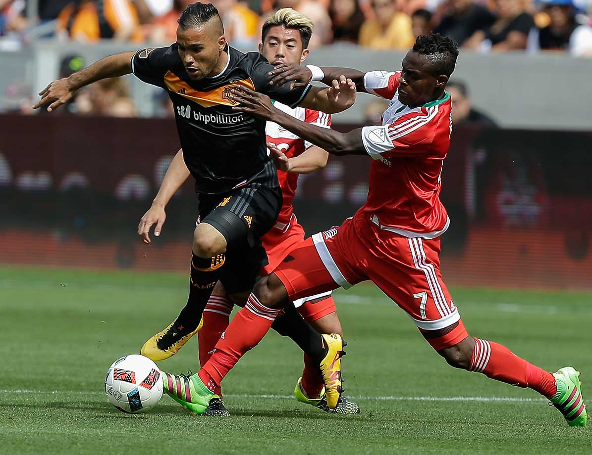 Alex of the Houston Dynamo dribbles between Gershon Koffie, 7, and Lee Nguyen of the New England Revolution.