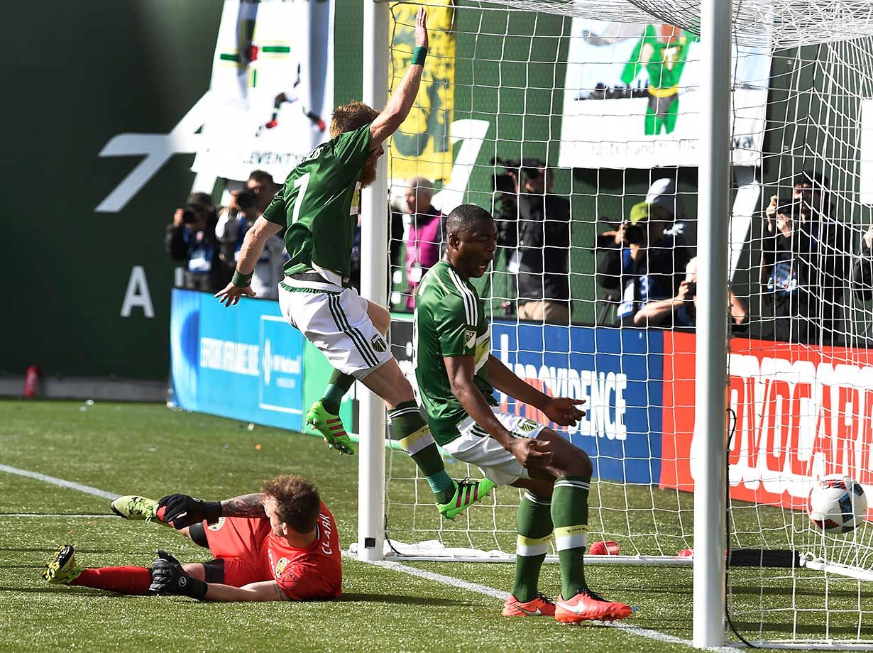 Nat Borchers of Portland Timbers leaps over Steve Clark of Columbus Crew as Fanendo Adi, right, follows the ball into the goal.