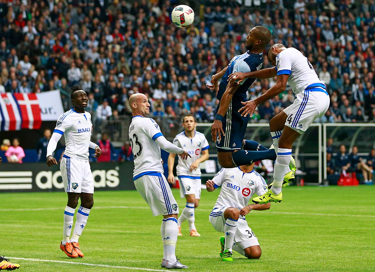 Kendall Waston of the Vancouver Whitecaps and Anthony Jackson-Hamel of the Montreal Impact head the ball.