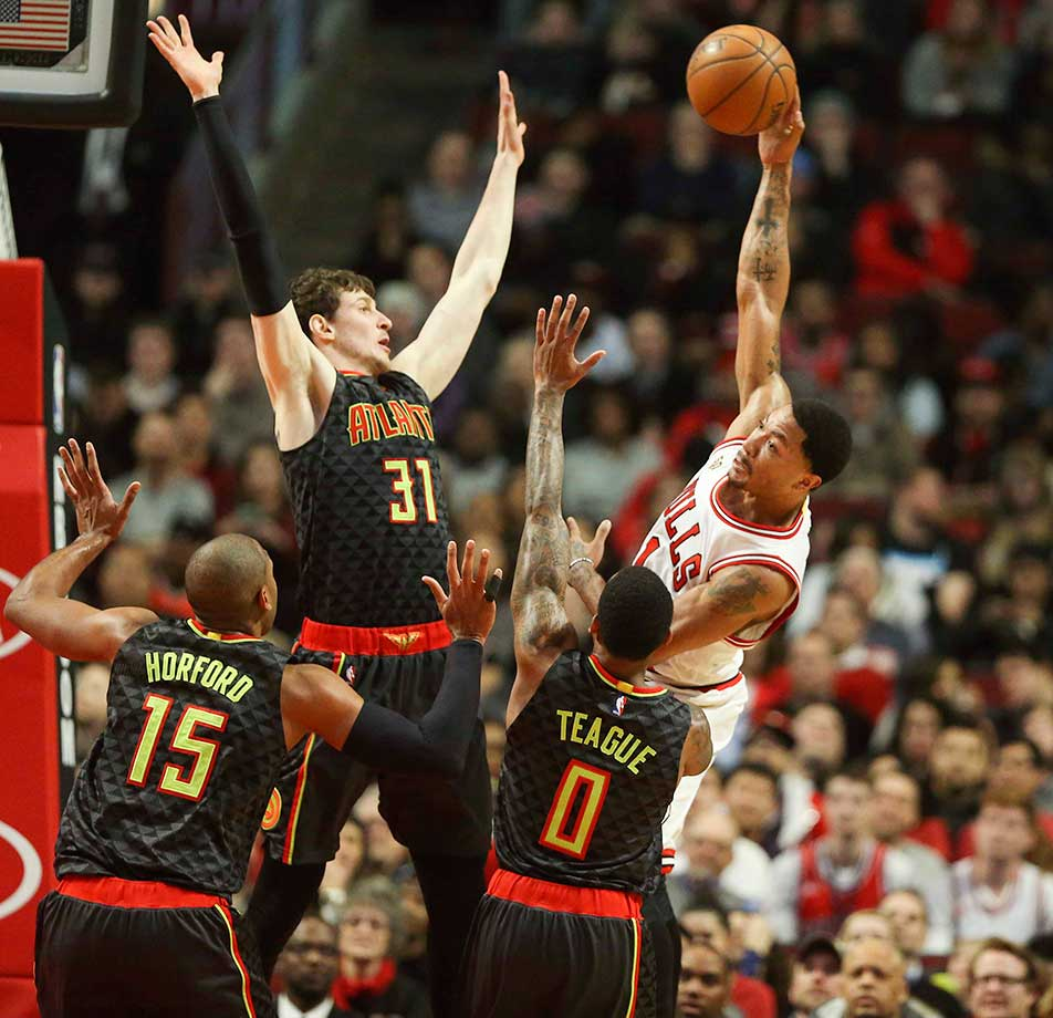 Derrick Rose makes a pass over Mike Muscala (31), Al Horford (15) and Jeff Teague of Atlanta.