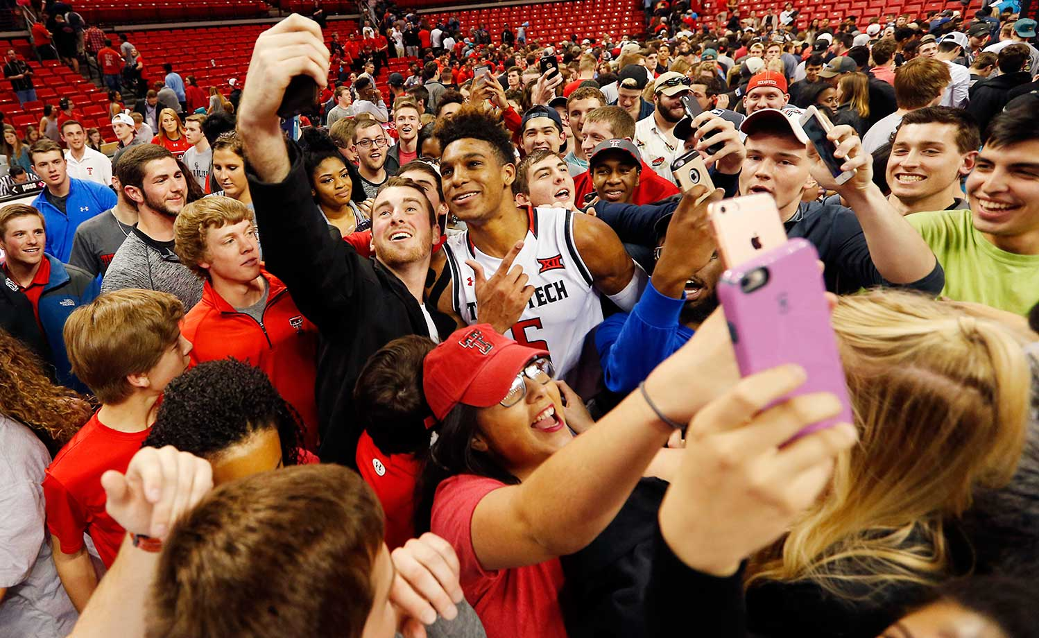 Texas Tech forward Justin Gray poses for photos with fans after Tech defeated Iowa State 85-82 in overtime.