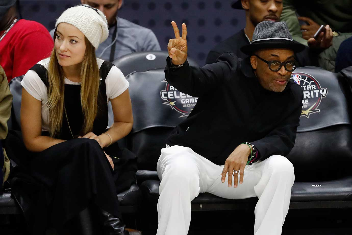 Sitting by actress Olivia Wilde, film director Spike Lee waves during the celebrity game at NBA All-Star weekend in Toronto.