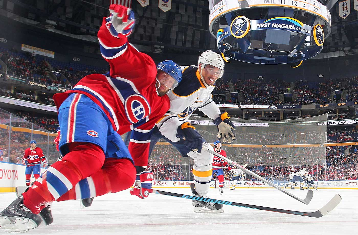 Evander Kane of the Buffalo Sabres battles for the puck against Tom Gilbert of the Montreal Canadiens.