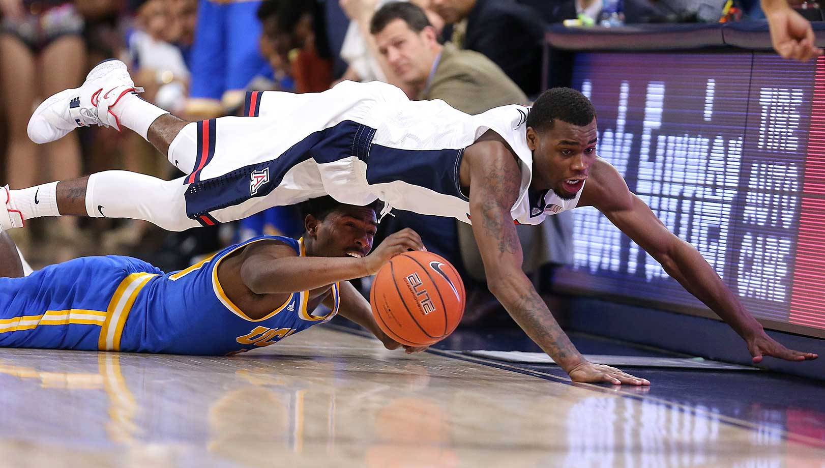 Kadeem Allen of Arizona dives over Isaac Hamilton of the UCLA Bruins.