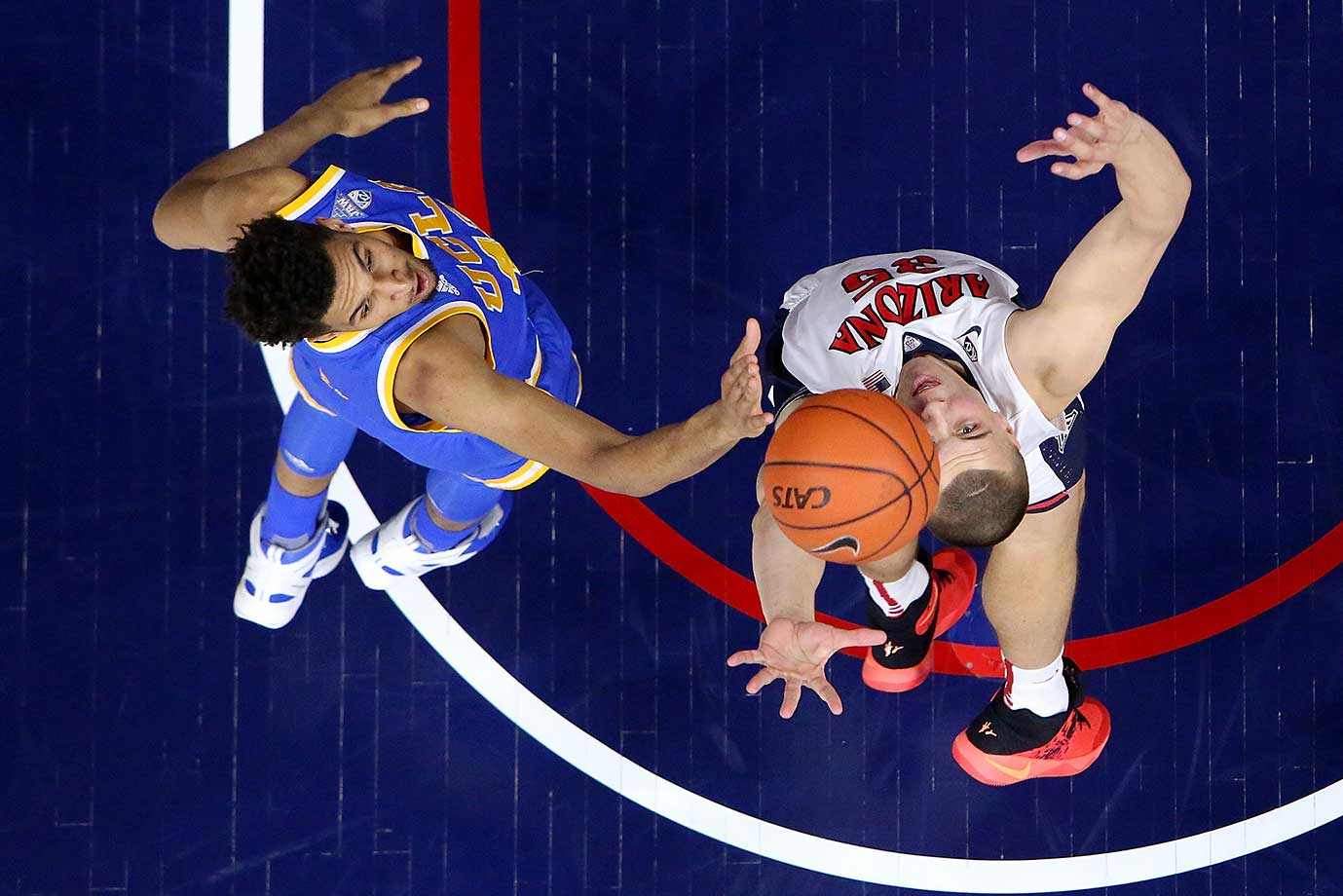 Kaleb Tarczewski of Arizona and Jonah Bolden of UCLA fight for a rebound.