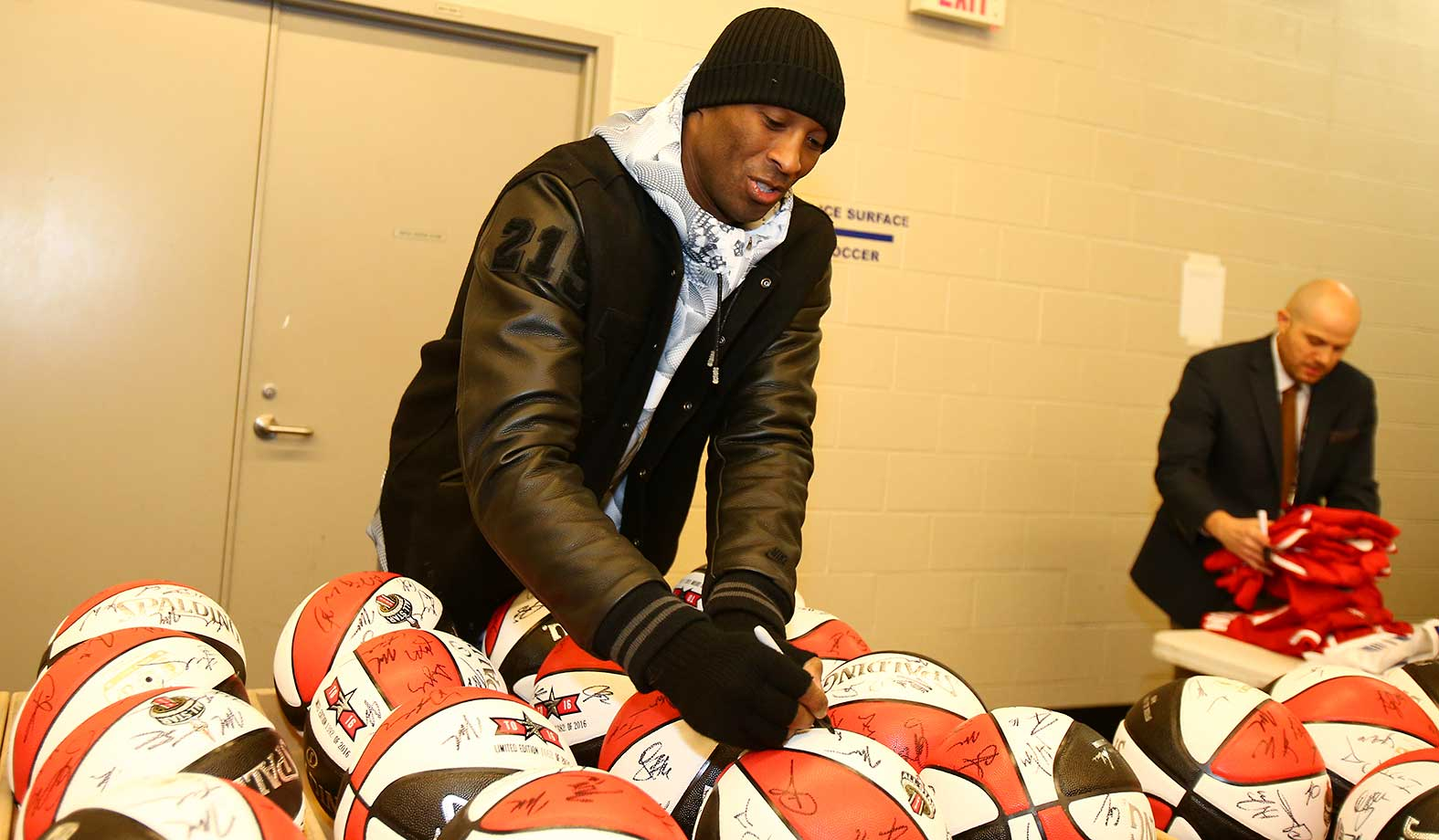 Kobe Bryant of the Western Conference All-Stars autographs basketballs before the NBA All-Star Practice.