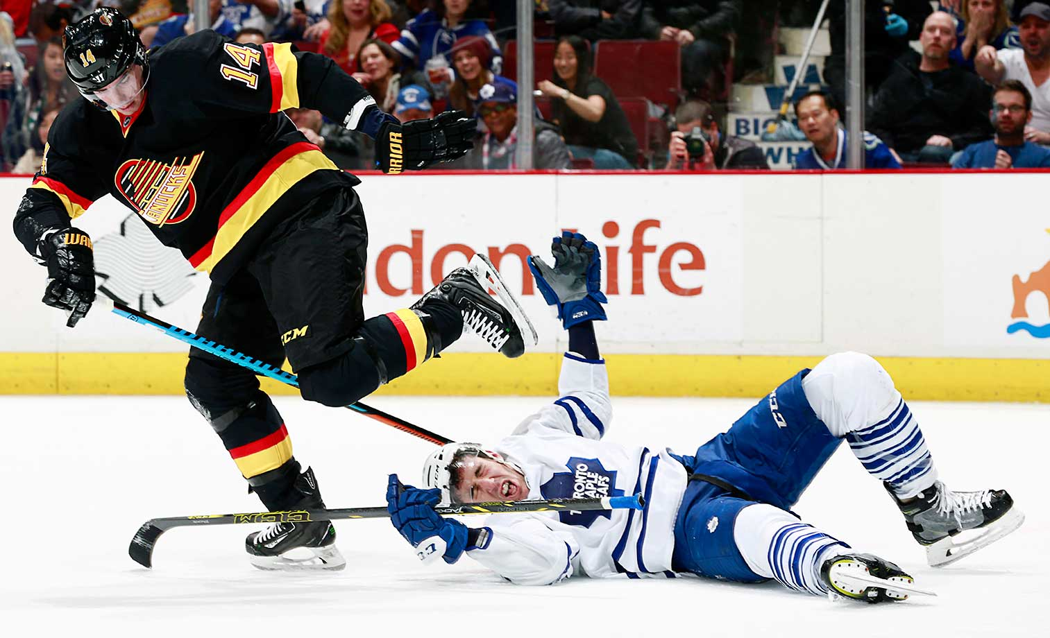 Alexandre Burrows of the Vancouver Canucks skates away after checking Frank Corrado of the Toronto Maple Leafs.