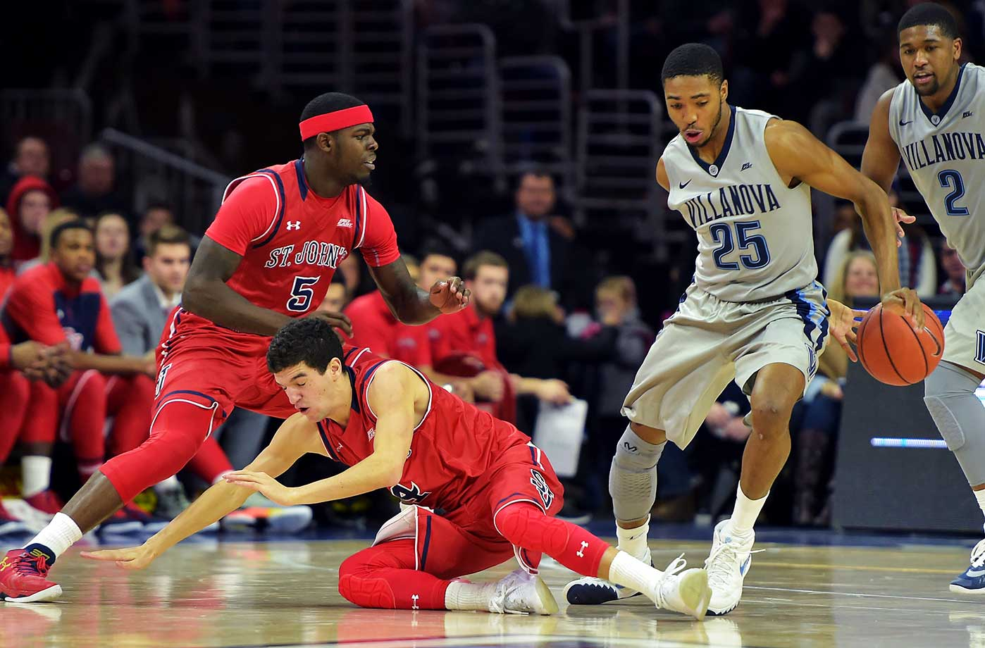 Mikal Bridges of the Villanova Wildcats crosses a fallen Federico Mussini of the St. John's Red Storm.