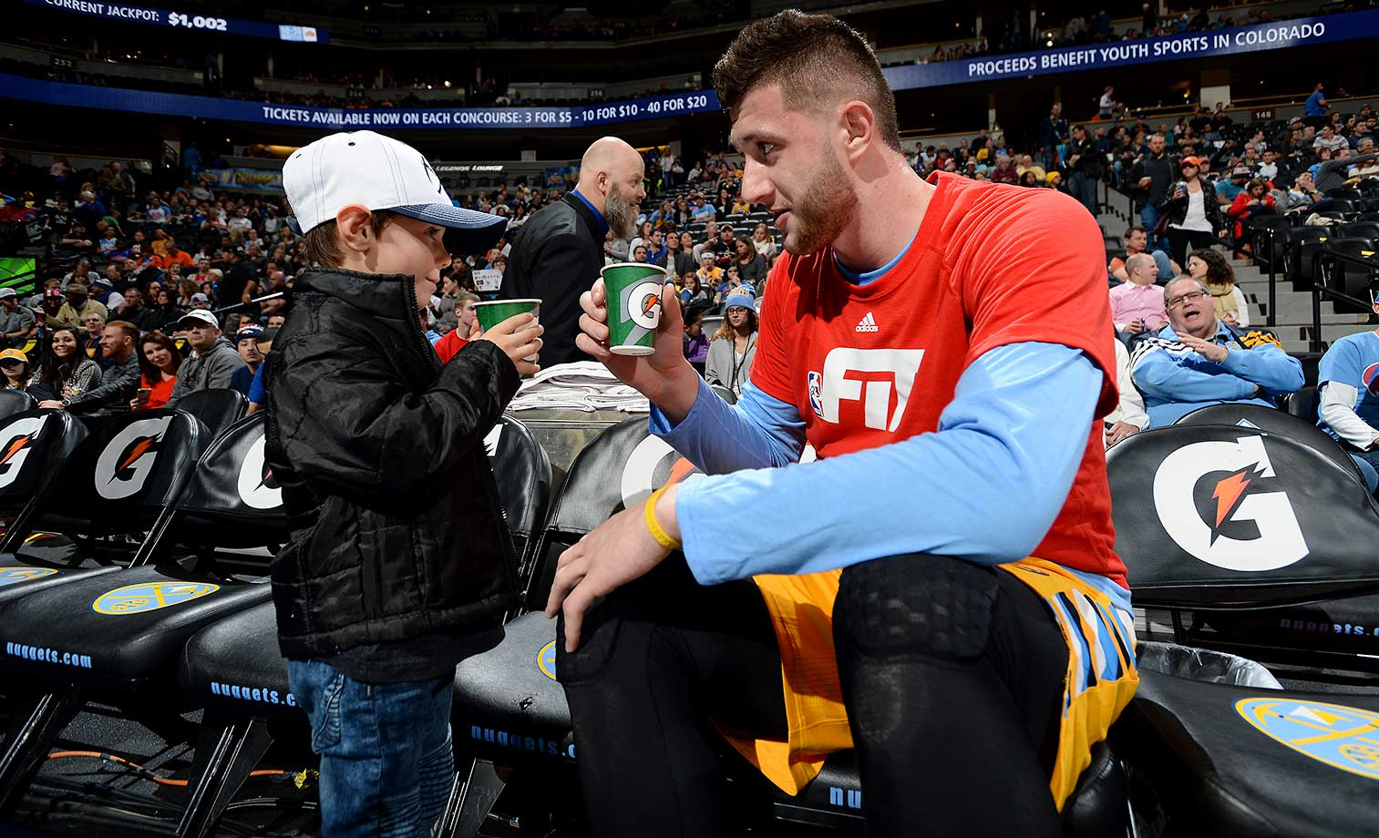 Jusuf Nurkic of the Denver Nuggets talks with a young fan before the game against the Detroit Pistons.