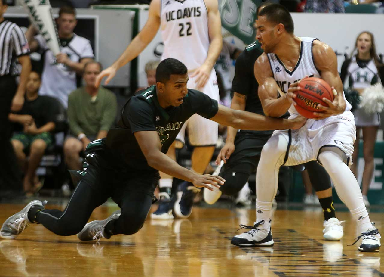 Sai Tummala of the Hawai'I Rainbow Warriors attempts to steal the ball away from Josh Fox of the UC Davis Aggies at the Stan Sheriff Center in Honolulu.