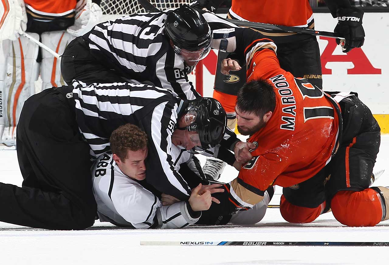 Brayden McNabb of the Los Angeles Kings mixes it up with Patrick Maroon of the Anaheim Ducks as linesman Matt MacPherson  and linesman Shane Heyer intervene at Honda Center in Anaheim.
