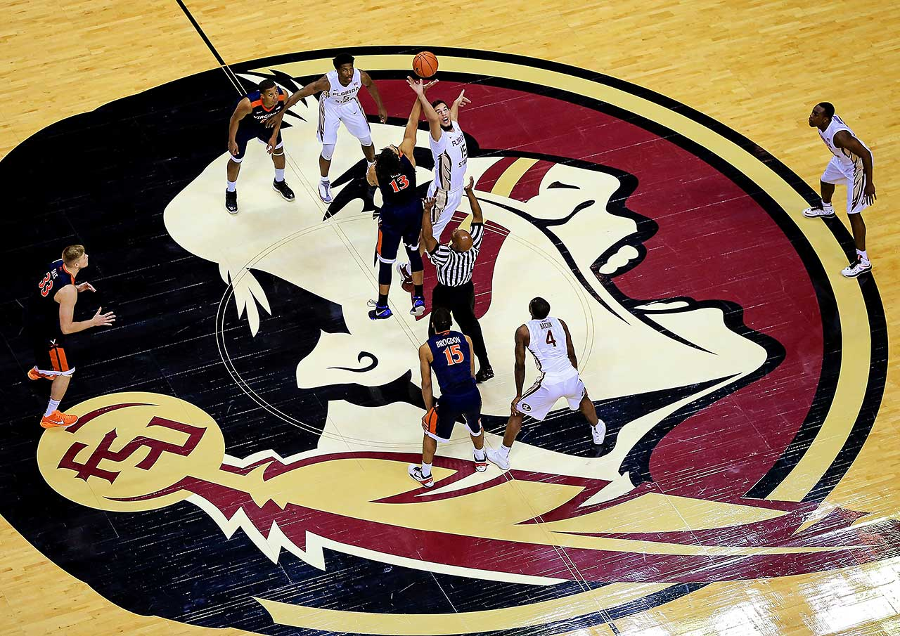 Boris Bojanovsky of the Florida State Seminoles and Anthony Gill of the Virginia Cavaliers tip off to start the game at the Donald L. Tucker Center in Tallahassee.