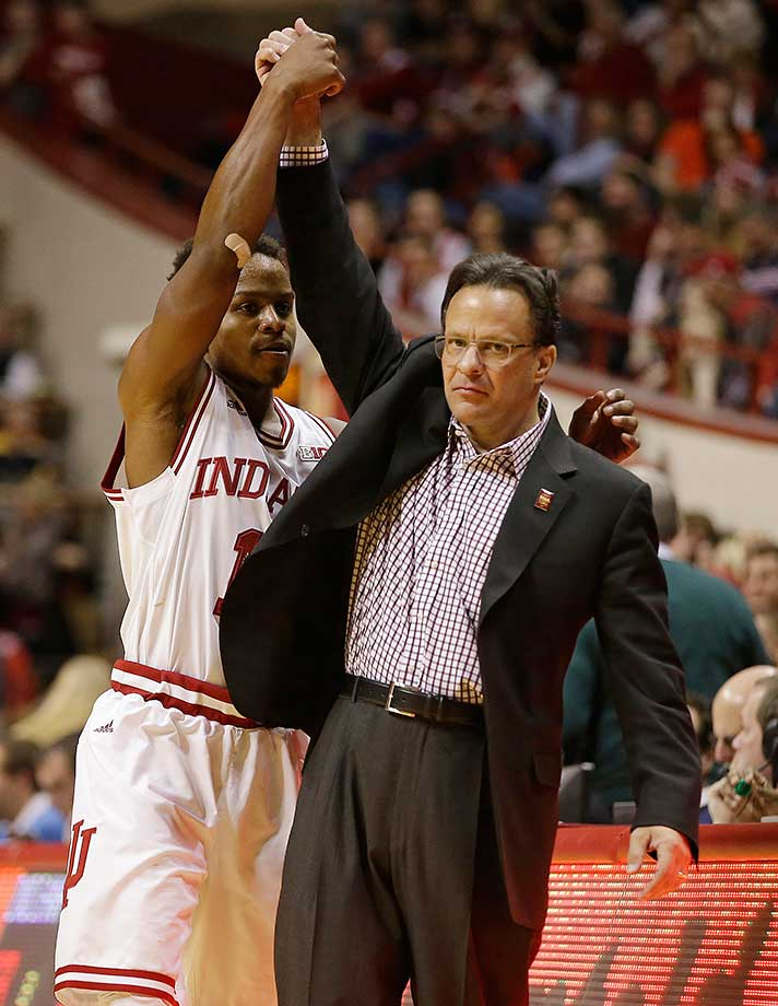 Indiana coach Tom Crean lifts the arm of Yogi Ferrell after the senior came out of the game on a night when he broke the school record for alltime assists. He picked up his 546th during Indiana's 103-69 victory.