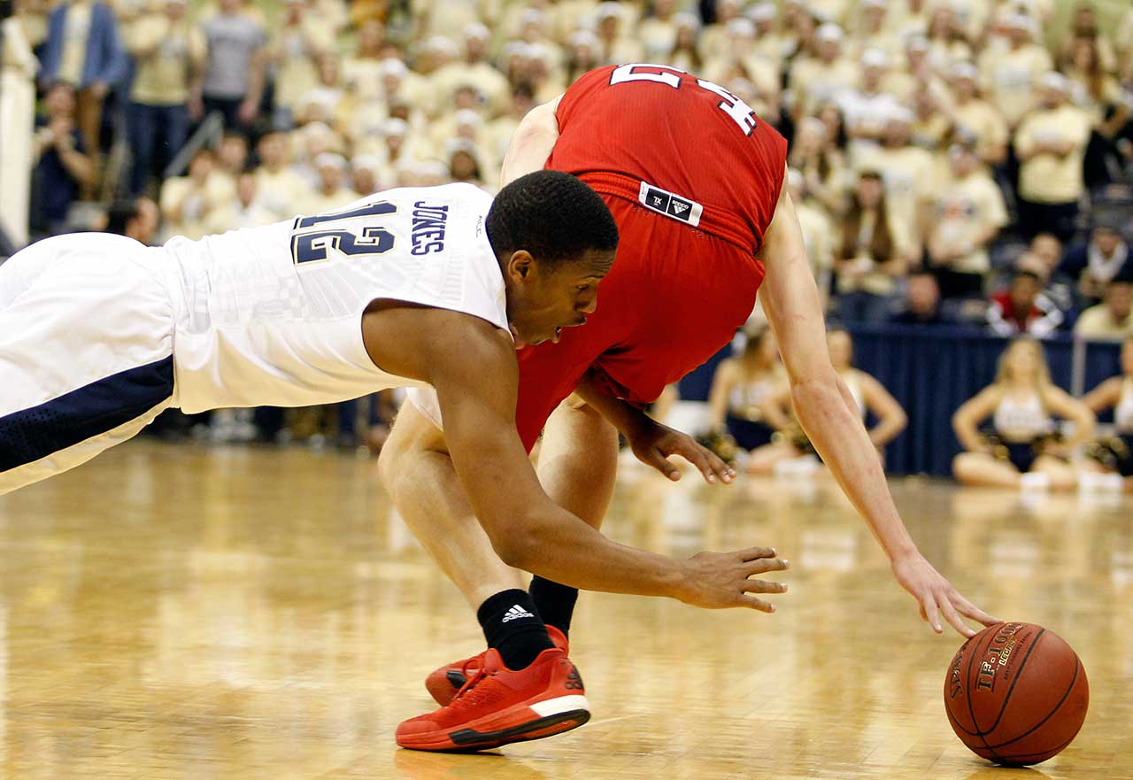 Chris Jones of the Pittsburgh Panthers and Maverick Rowan of the North Carolina State Wolfpack battle for a loose ball.