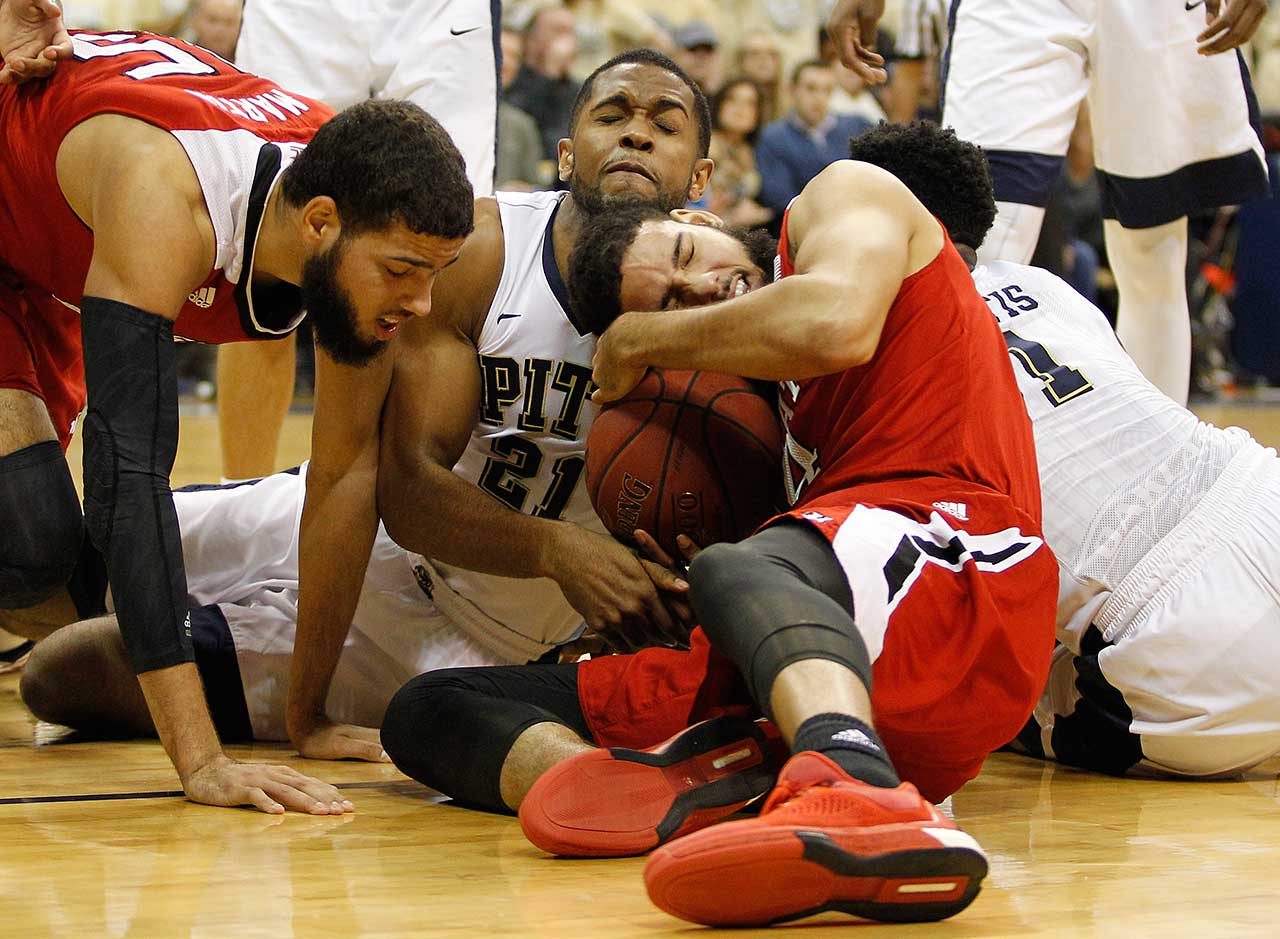 Sheldon Jeter of the Pittsburgh Panthers and Caleb Martin of the North Carolina State Wolfpack battle for a loose ball.