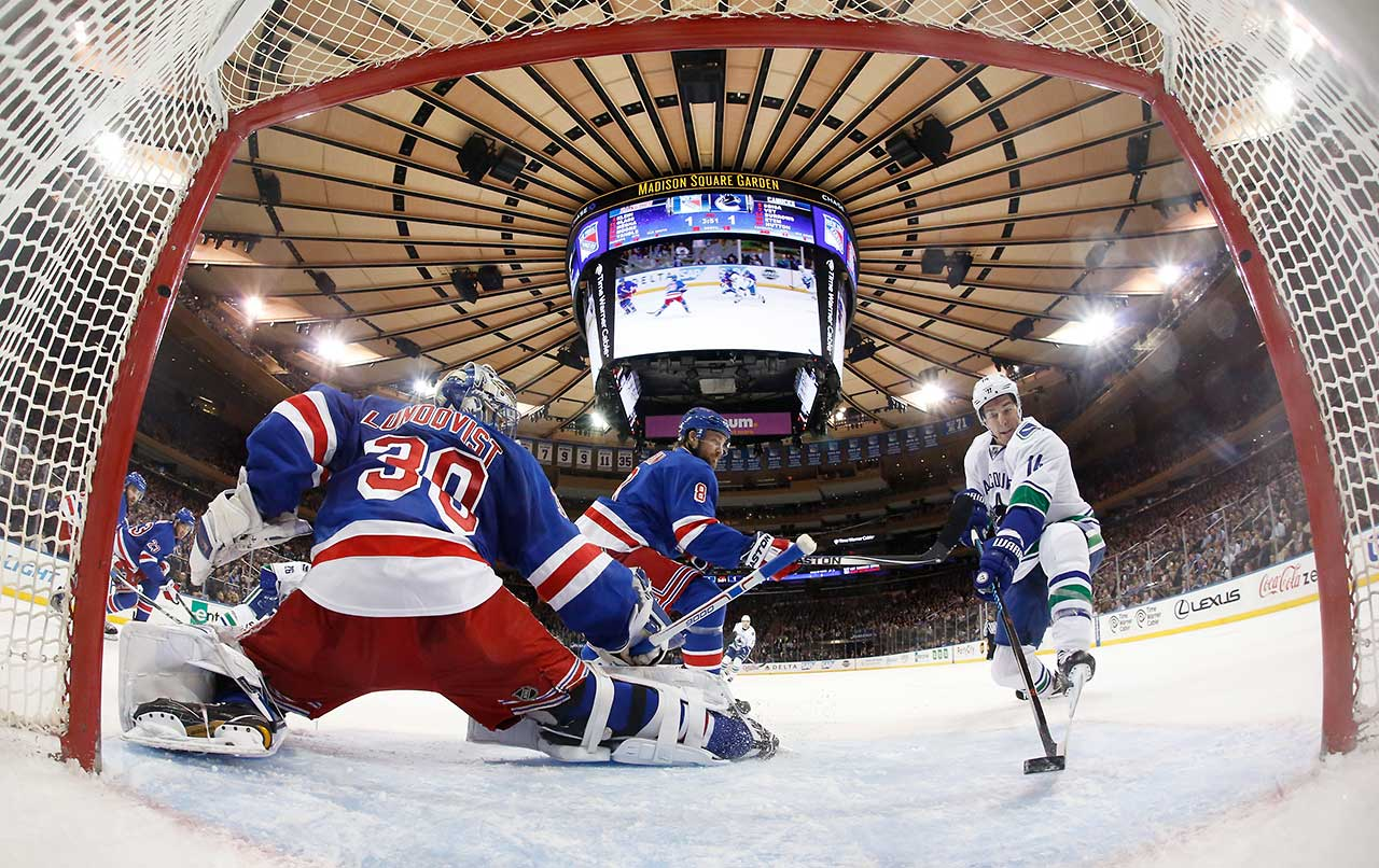 Alex Burrows of the Vancouver Canucks redirects the puck into the net past Henrik Lundqvist of the New York Rangers at Madison Square Garden.
