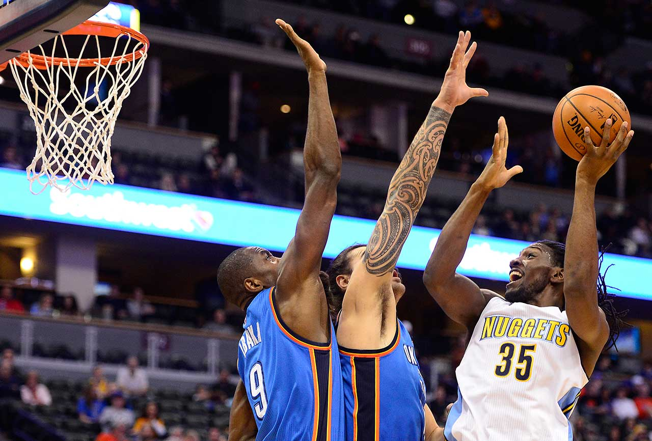 Kenneth Faried of the Denver Nuggets puts up a hook shot over Oklahoma City Thunder defenders at the Pepsi Center in Denver.