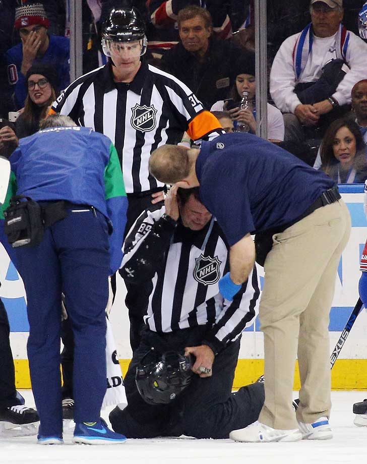 Linesman Steve Miller hits the ice after being hit with the puck during the game between the Vancouver Canucks and the New York Rangers at Madison Square Garden.