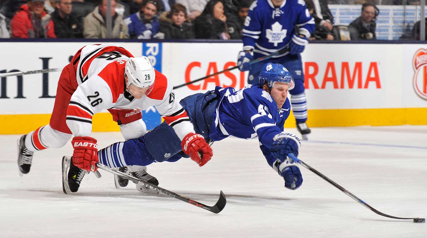Leo Komarov of the Toronto Maple Leafs and John-Michael Liles of the Carolina Hurricanes dive after the puck at Air Canada Centre in Ontario.