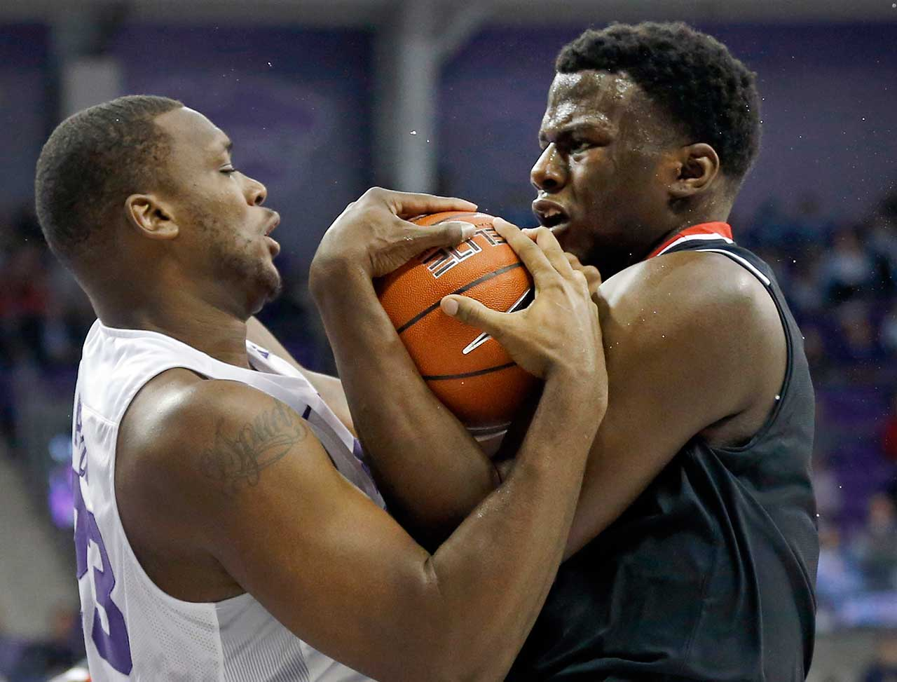 TCU forward Devonta Abron and Texas Tech center Norense Odiase wrestle for a loose ball.