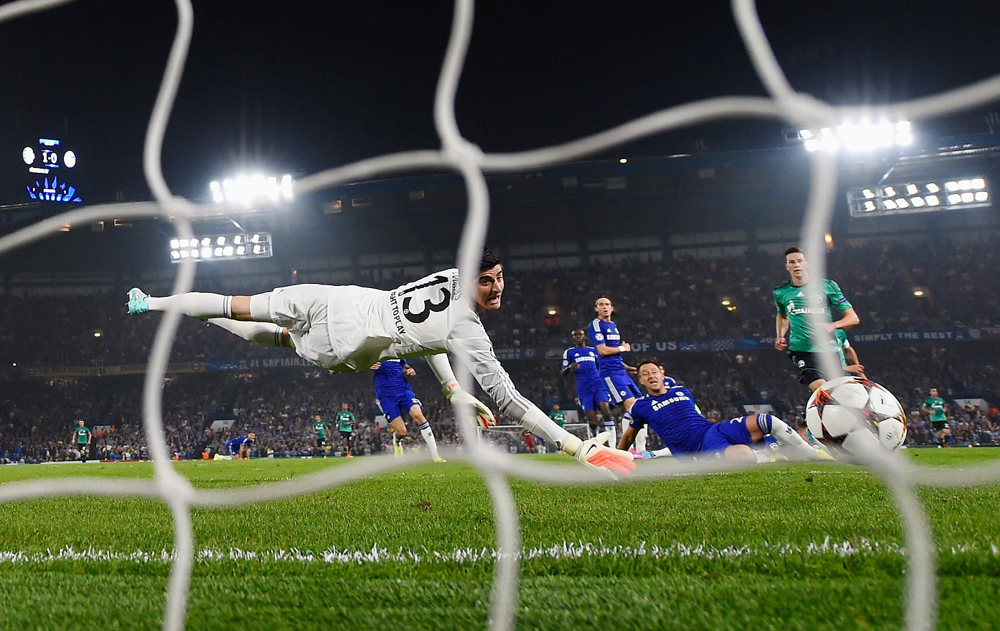 Thibaut Courtois of Chelsea dives in vain as Klaas-Jan Huntelaar of Schalke scores a goal during the UEFA Champions League Group G match.