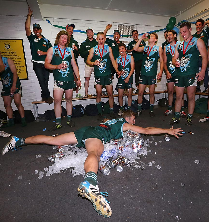 Tom McArlein of Geelong dives on iced beers after a victory during the Bellarine Football League Grand Final match between Geelong Amateurs and Ocean Grove.