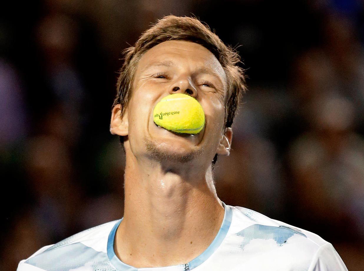 Tomas Berdych of the Czech Republic bites a ball during his semifinal match against Andy Murray at the Australian Open.