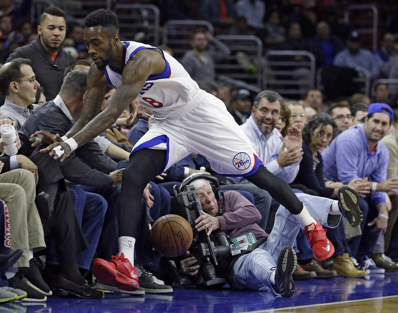 Philadelphia 76ers' Tony Wroten collides with a cameraman after chasing a loose ball into the seats during a 2014 game.