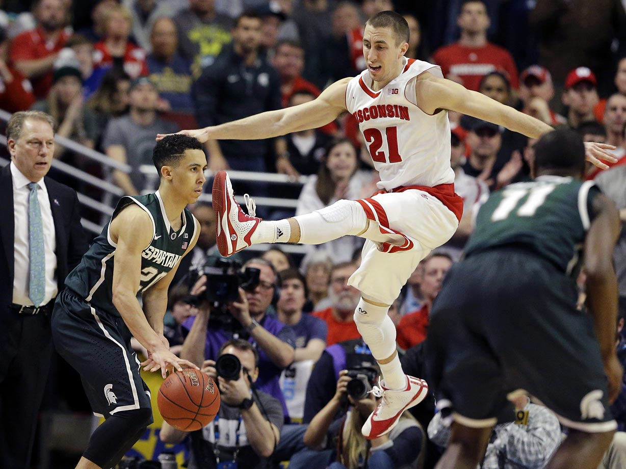 Travis Trice of Michigan State cuts under Josh Gasser of Wisconsin.  Wisconsin defeated Michigan State 80-69 in overtime.