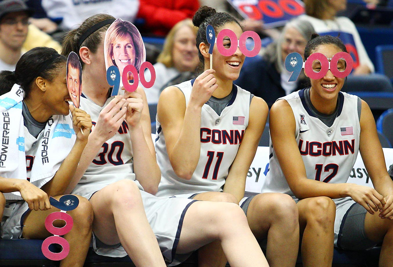 Starters for the UConn Huskies start to celebrate head coach Geno Auriemma's 900th career win.