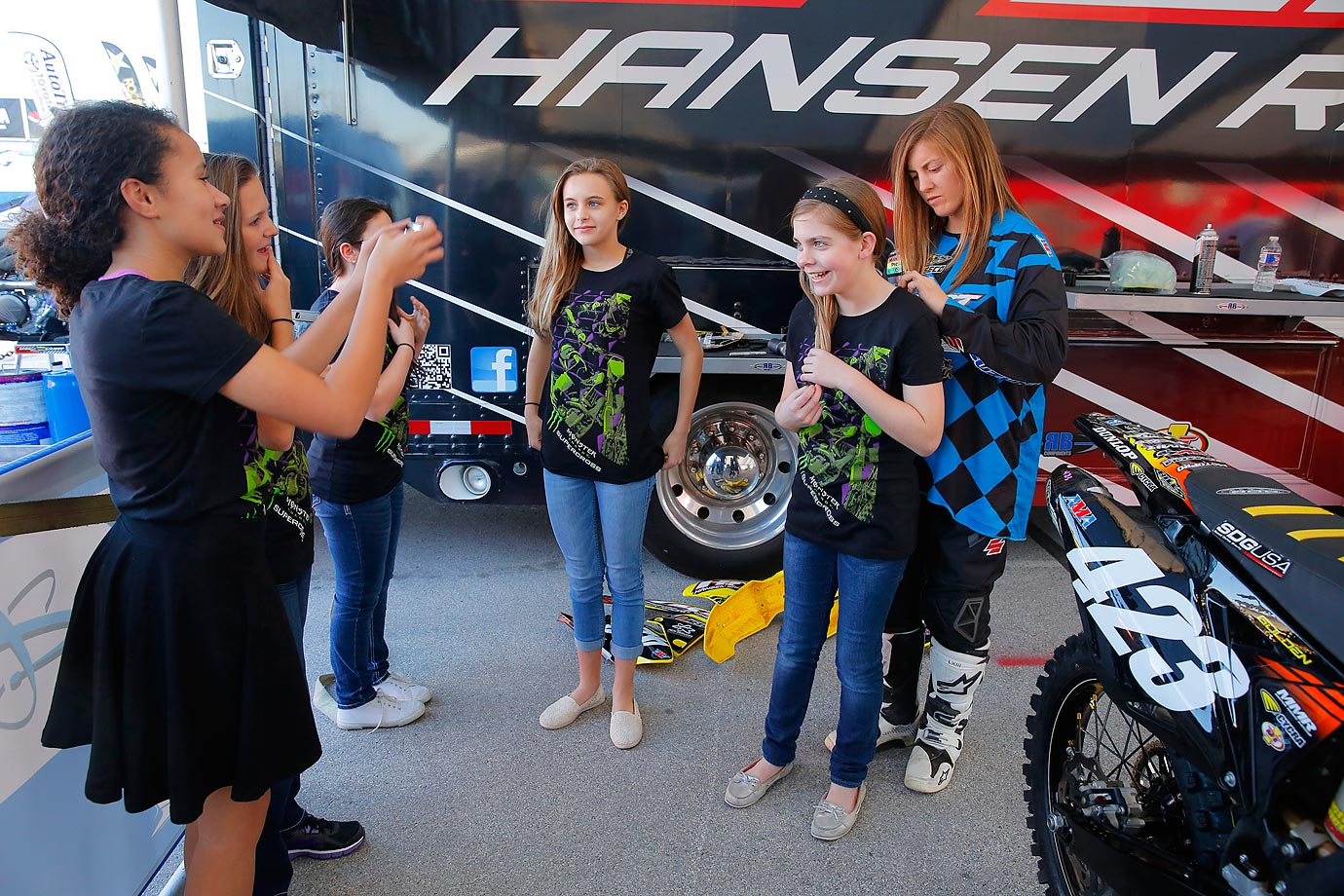 Golden signs some autographs for a local group of fans at her pit area trailer.