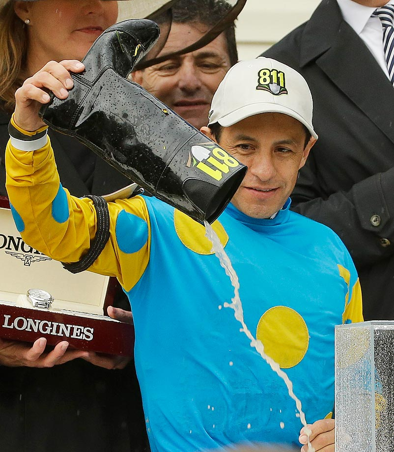 Victor Espinoza pours the water out of his boot after he and American Pharaoh won the 140th Preakness Stakes.