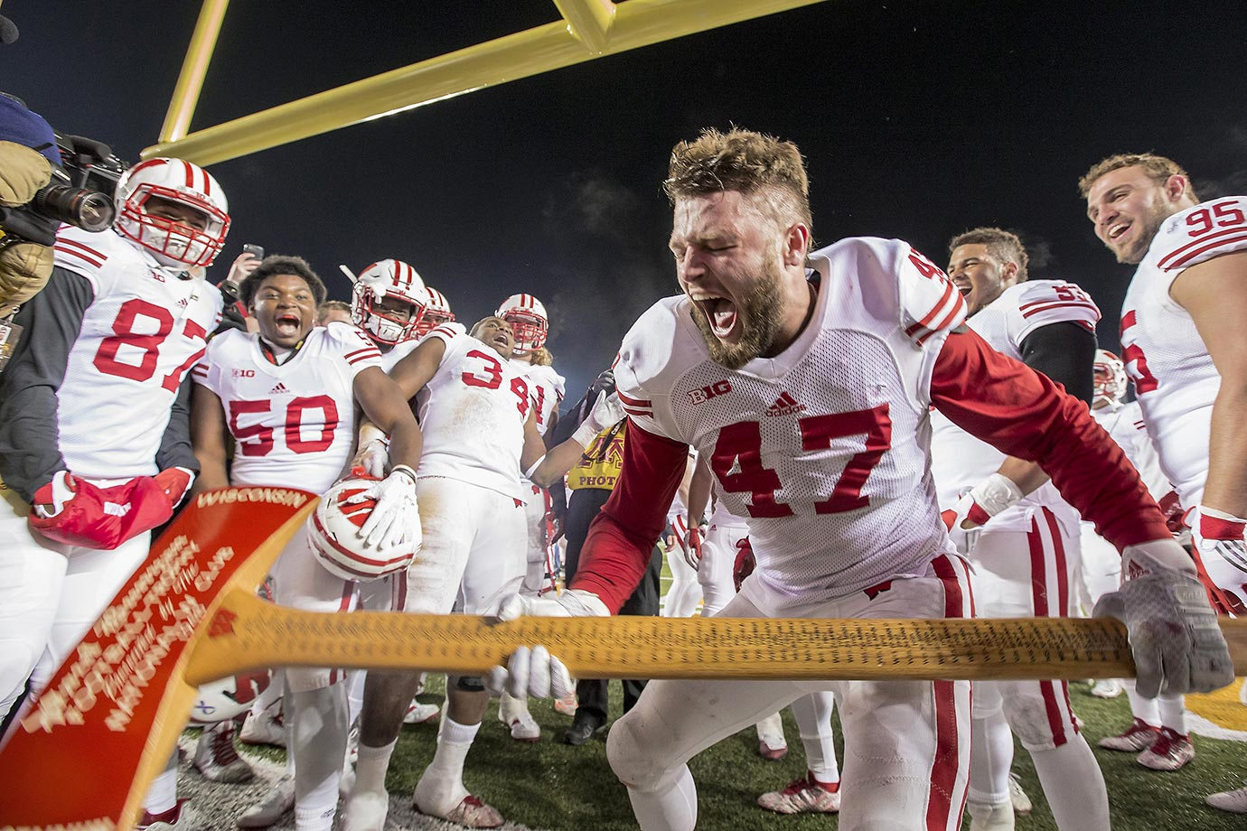 Vince Biegel of Wisconsin chops down the goal post after a game against the Minnesota Golden Gophers.