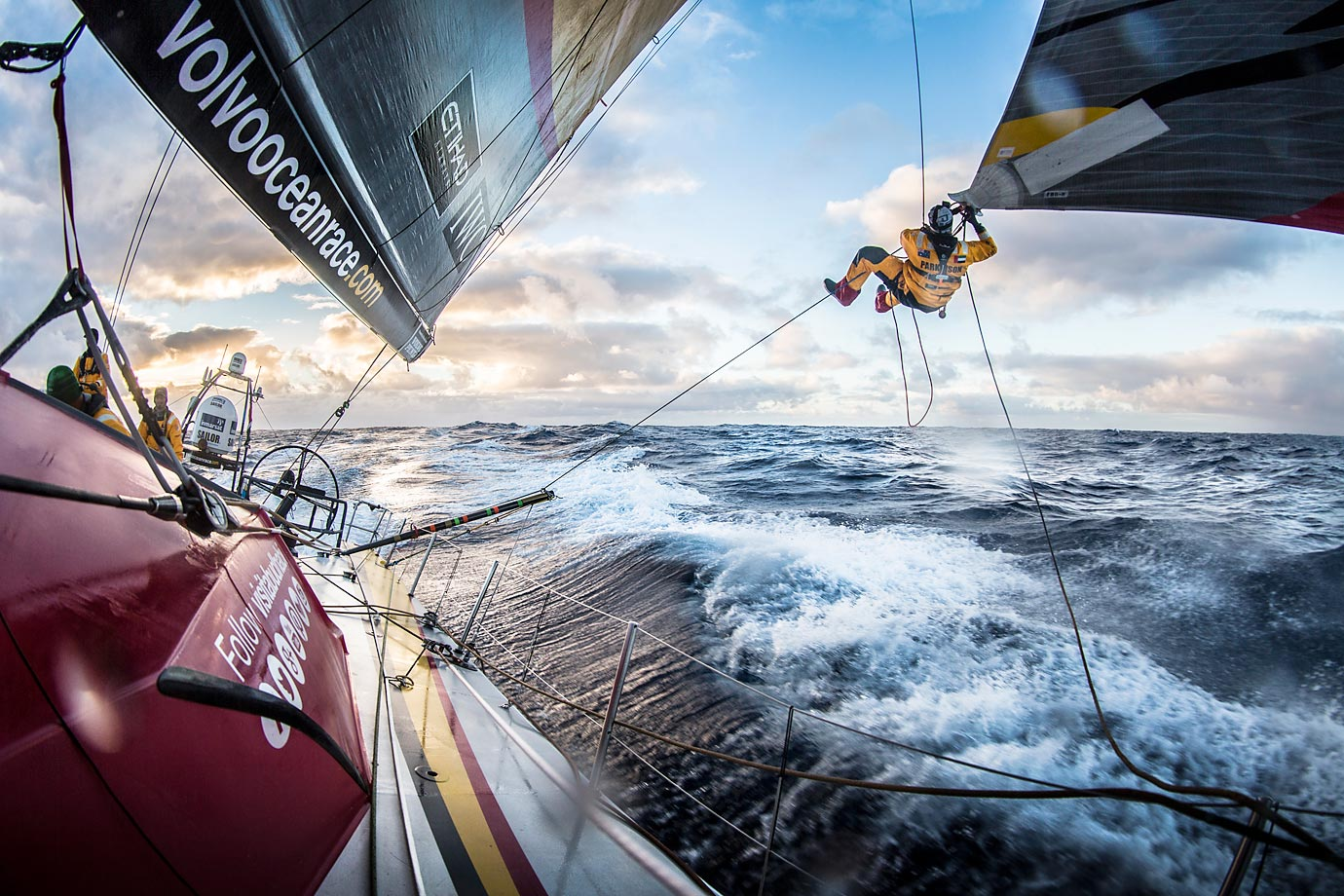"Luke ""Parko"" Parkinson swings out over the ocean to tie a changing sheet on the FRO at sunset during the Volvo Ocean Race."