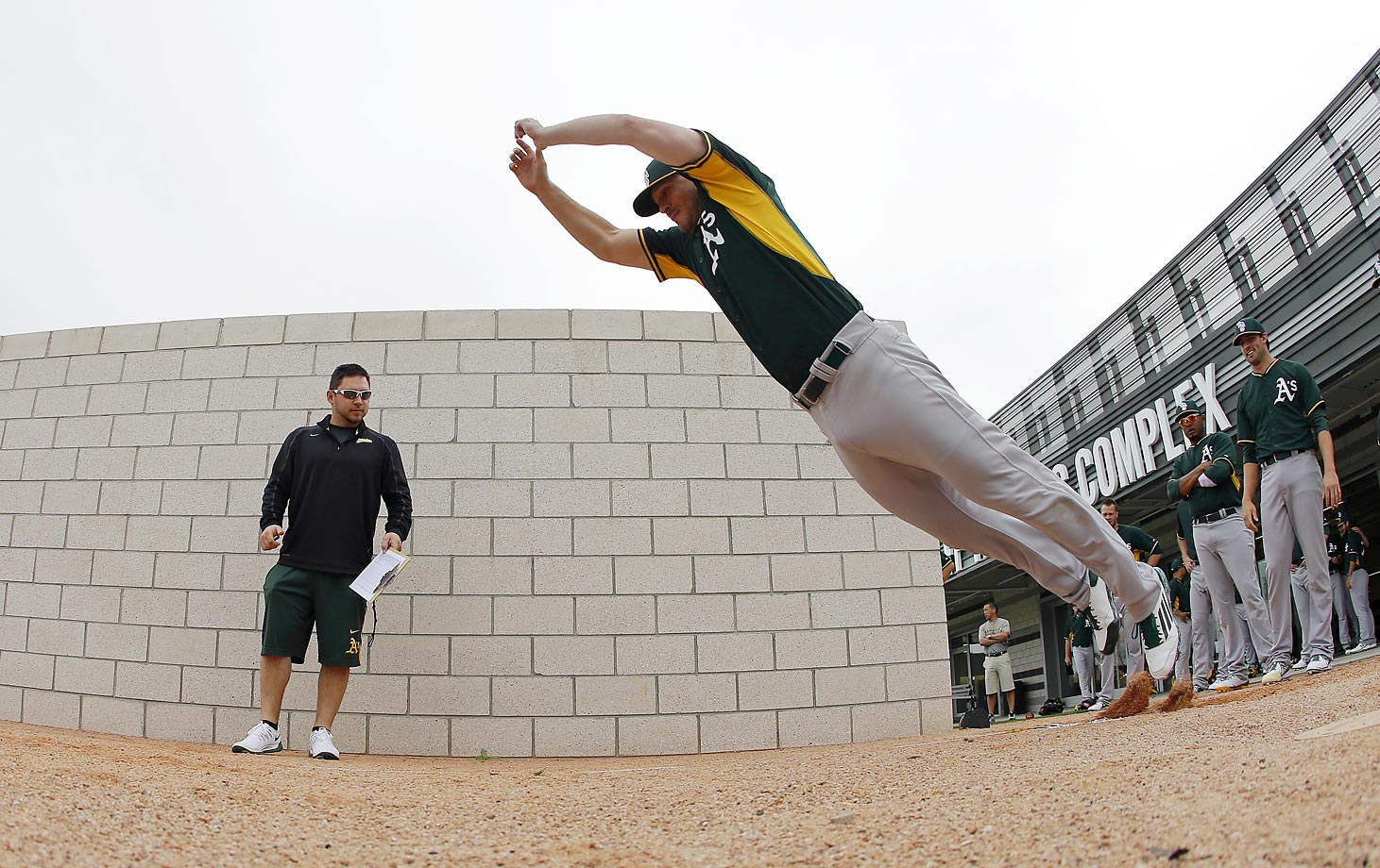 Oakland Athletics' Taylor Thompson leaps into spring training.  The A's are in Mesa, Ariz.