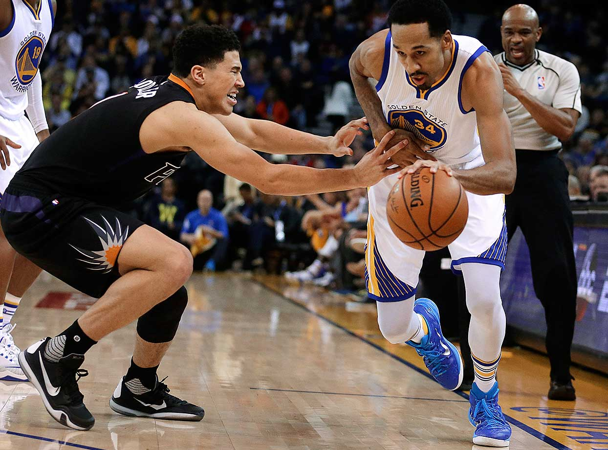 Shaun Livingston drives the ball against Devin Booker of the Phoenix Suns.
