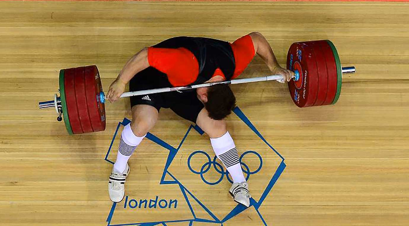 Matthias Steiner of Germany attempts to get from under the weights he dropped at the London 2012 Summer Olympic Games.