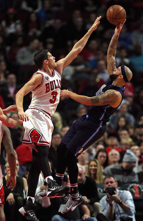 Deron Williams of the Dallas Mavericks shoots against Doug McDermott of the Chicago Bulls at the United Center.