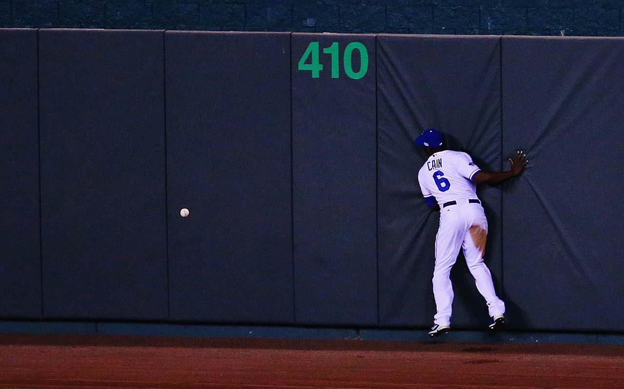 The ball bounced off Lorenzo Cain's glove before he slammed into the wall, enabling Pablo Sandoval to reach base on a double.